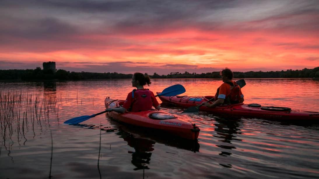 People kayaking  through still waters with beautiful sunset views