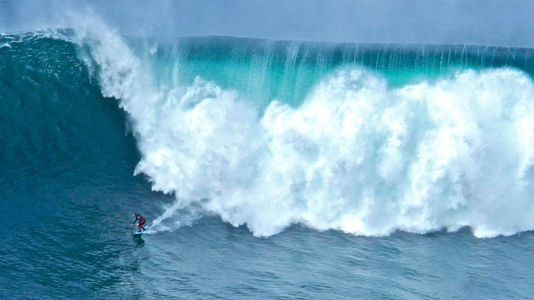 Surfer with a massive wave behind them in Sligo