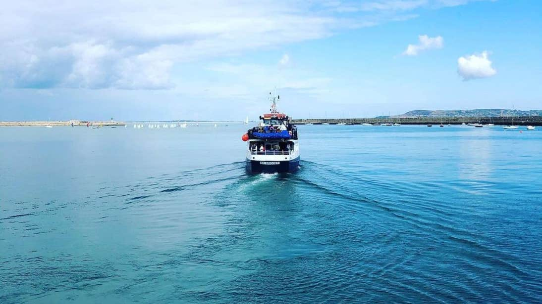 A cruiser out on Dublin Bay on a clear day with blue skies