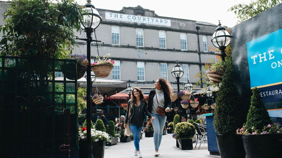 Two women strolling through The Courtyard in Cork City.