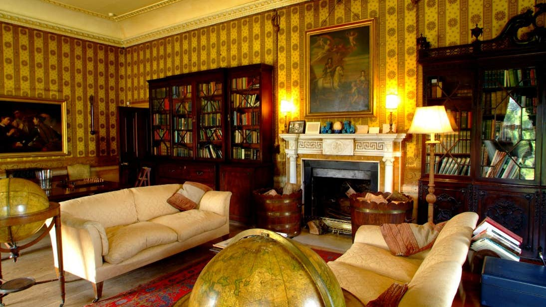 Paintings and books in a sitting room with white couches in Strokestown House, Roscommon