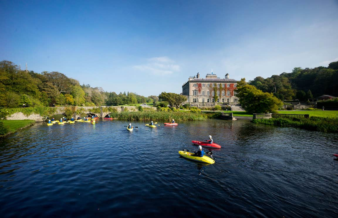 A group of people kayaking in front of Westport House, Mayo