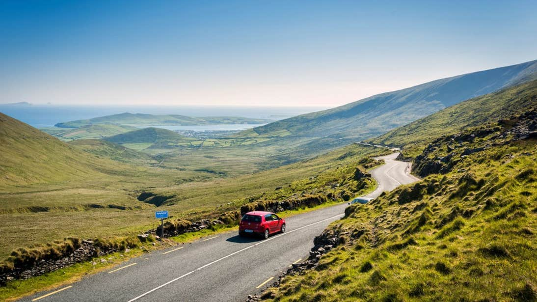 View of Conor Pass, Co. Kerry with a red car driving on the road