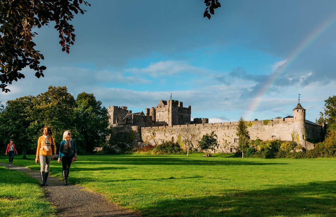 People walking on a path through a lawn outside Cahir Castle, Tipperary
