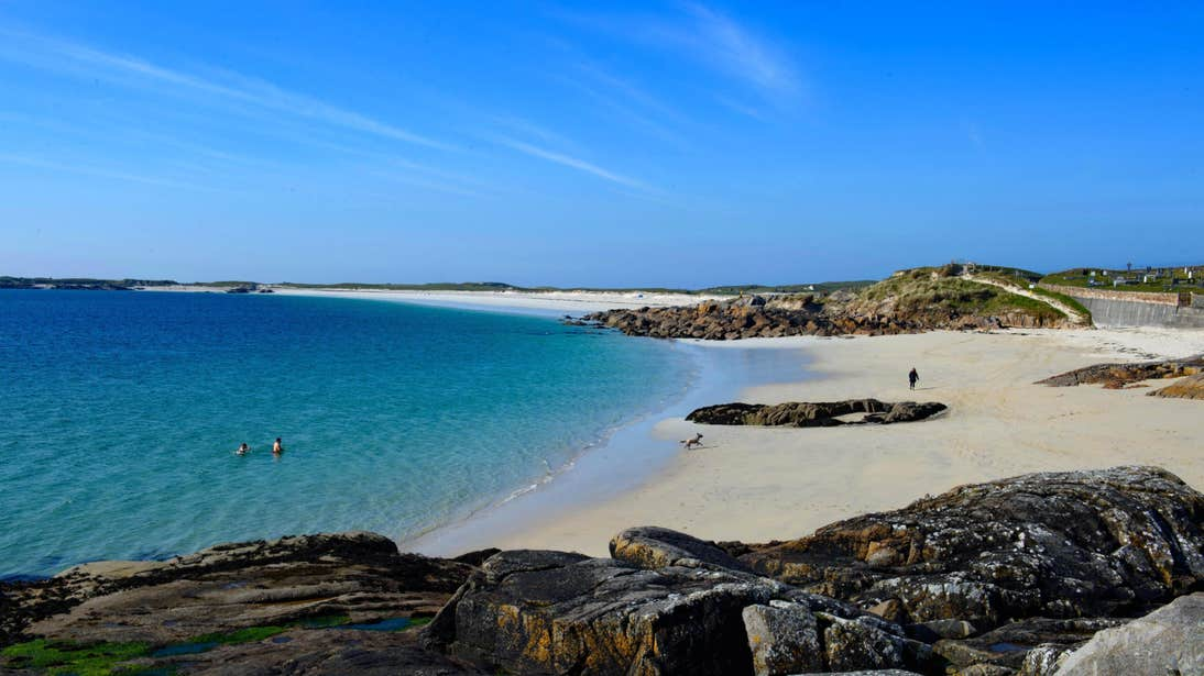 Two people bathing in clear blue water while a dog walks on the shore at Gurteen Beach in Galway