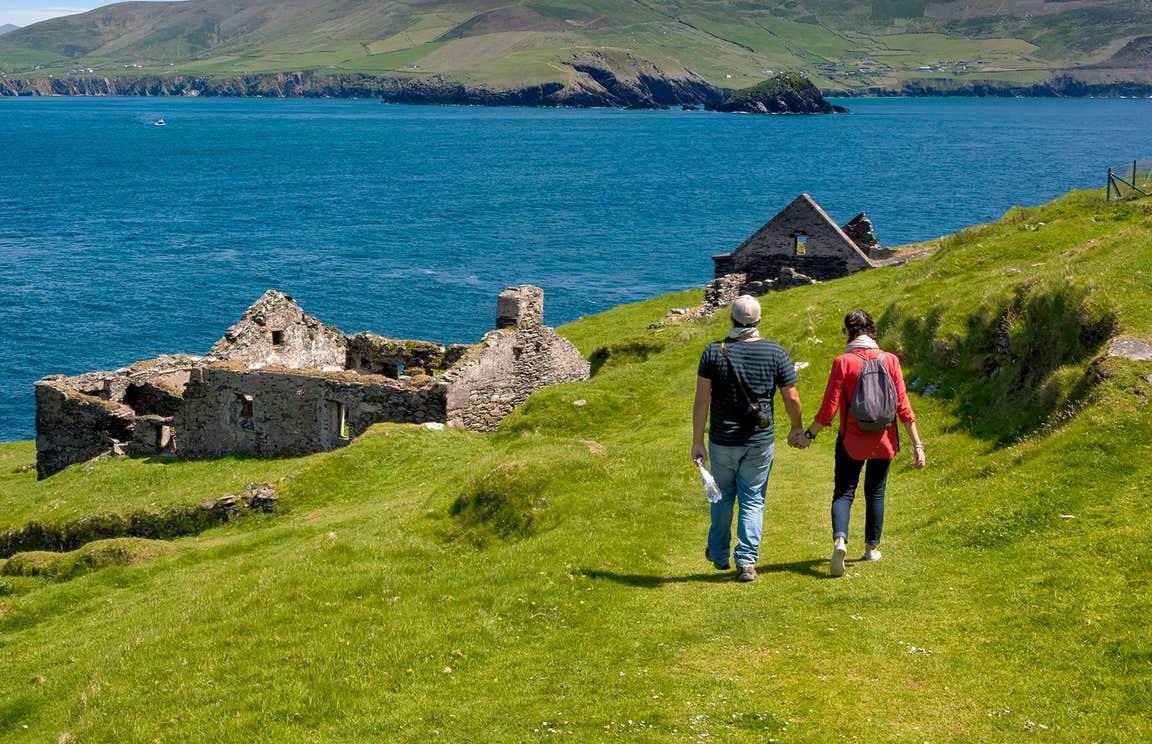 Two hikers walking on a grassy trail near abandoned buildings on Blasket Islands, Kerry.