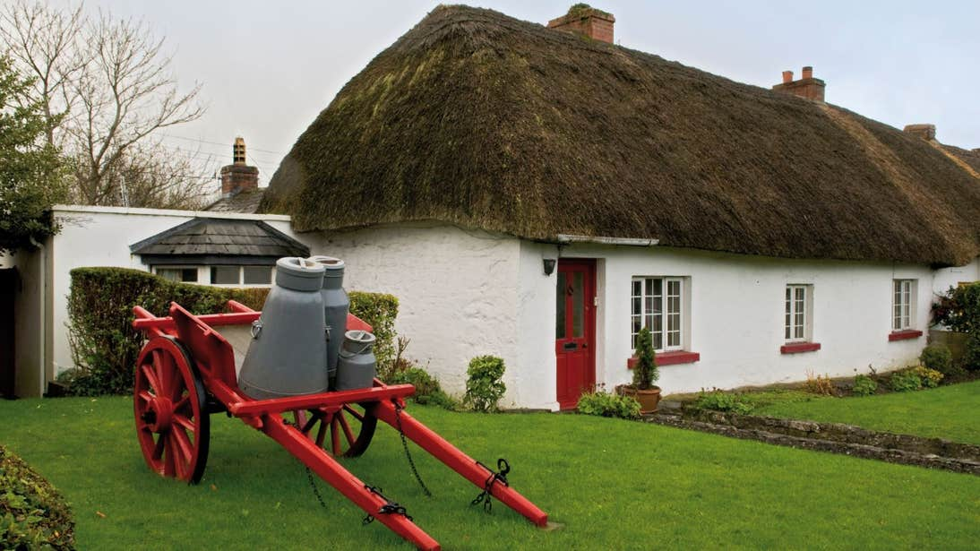 Green grass outside a thatched cottage in Adare, Co. Limerick
