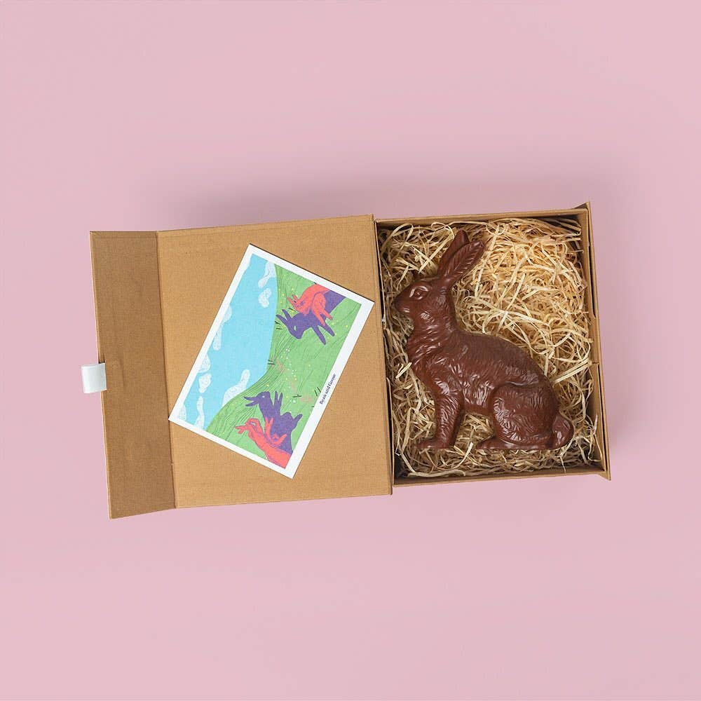 A chocolate rabbit in a cardboard box on a bright pink background, made by Bean and Goose