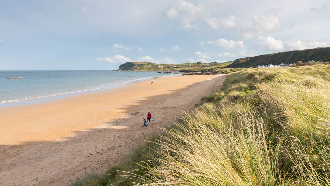 Two people walking down a quiet stretch of Culdaff Beach, County Donegal