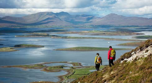 Two hikers on Croagh Patrick in Mayo near the waters of Clew Bay