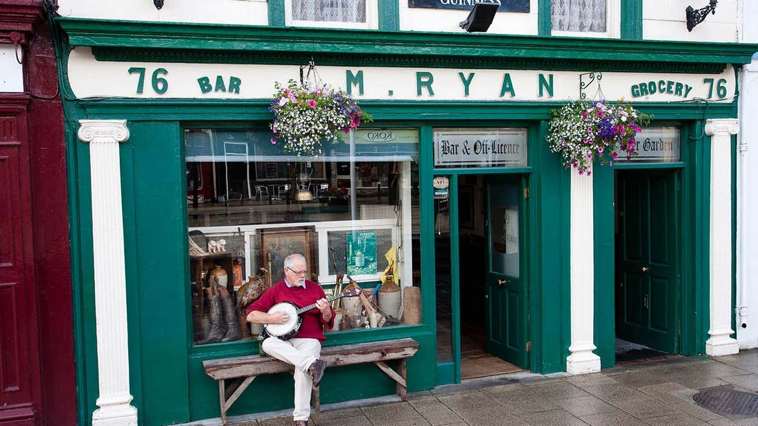 Man playing a banjo outside a green pub in Cashel