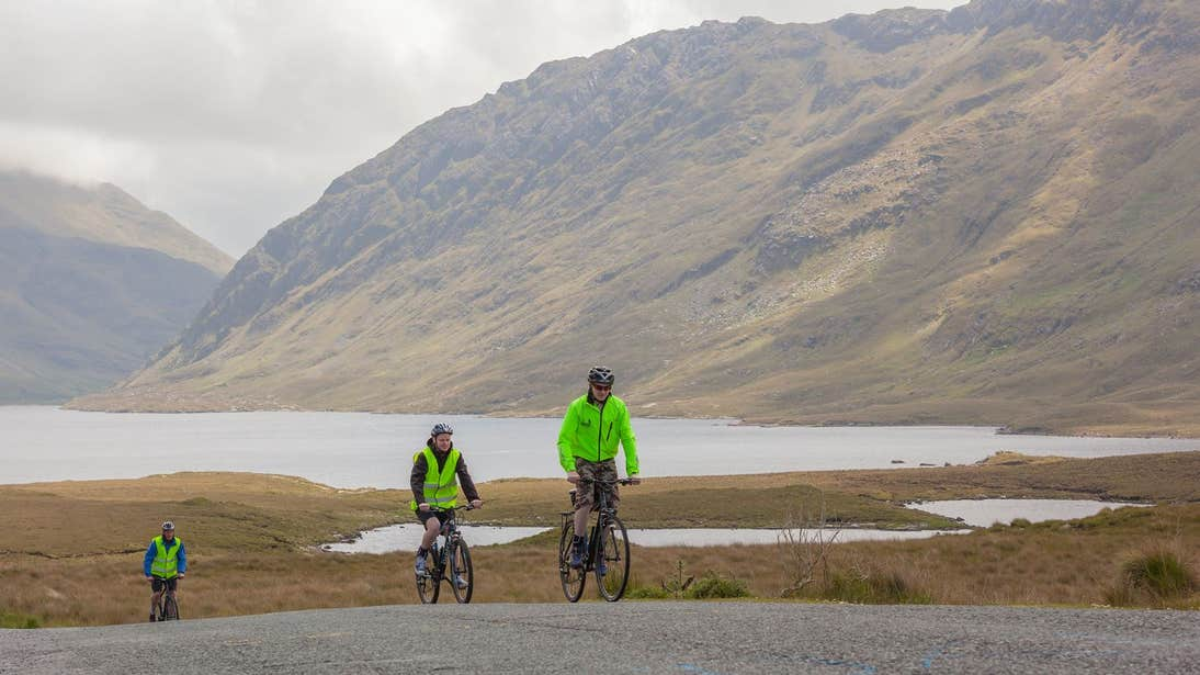 Two cyclists with a backdrop of magnificent mountain views