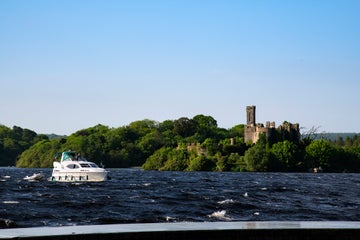 A boat sailing past a castle on Lough Key in Roscommon