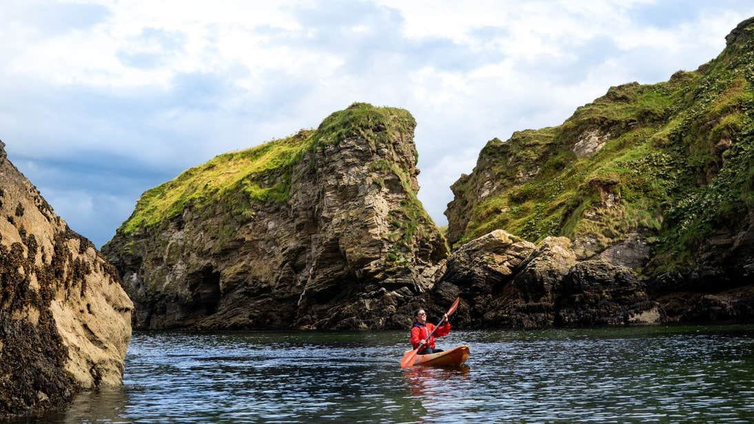 A person in a kayak with cliffs in the backdrop