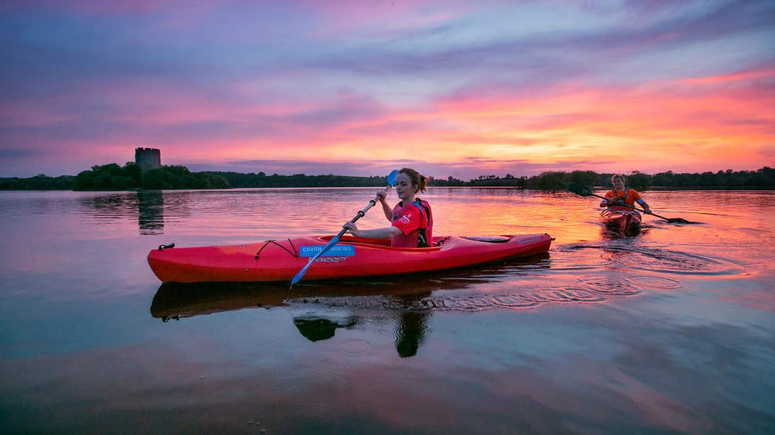 Two people kayaking at sunset on Lough Oughter