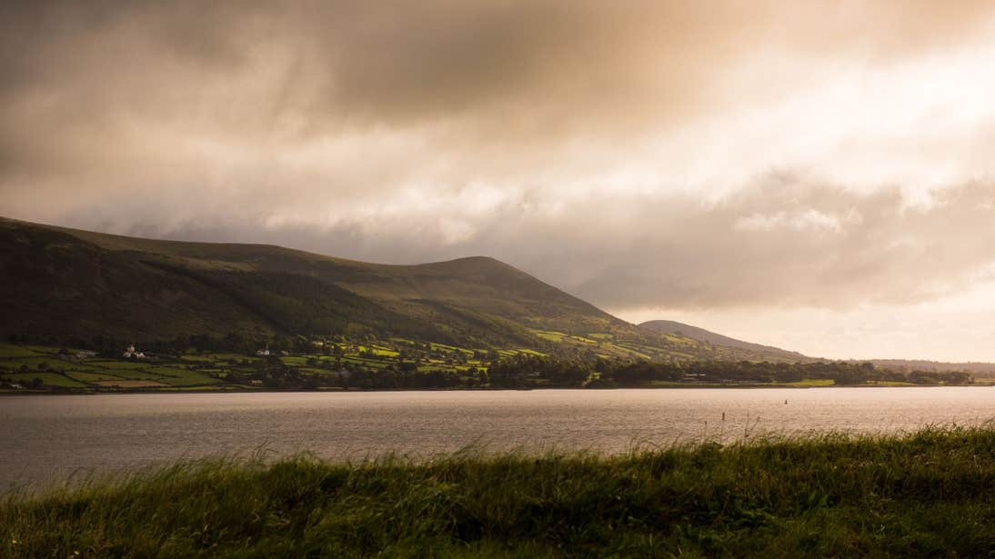 A peaceful Carlingford Lough with a backdrop of green fields and mountains