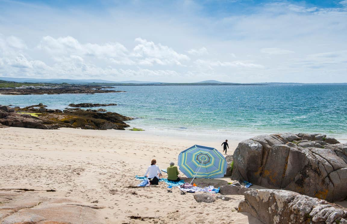 A group of people on Gurteen Beach, Galway on a sunny day