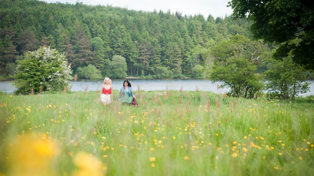 Two people walking through a meadow beside Lough Muckno in Monaghan