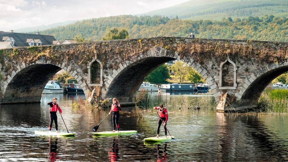 Three people paddle boarding along the River Barrow in Graiguenamanagh, Kilkenny.