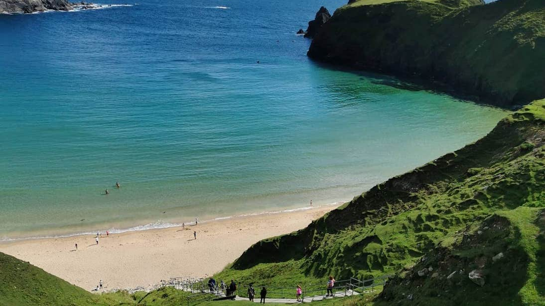 People walking down the steps to the beach at Malin Beg, Donegal