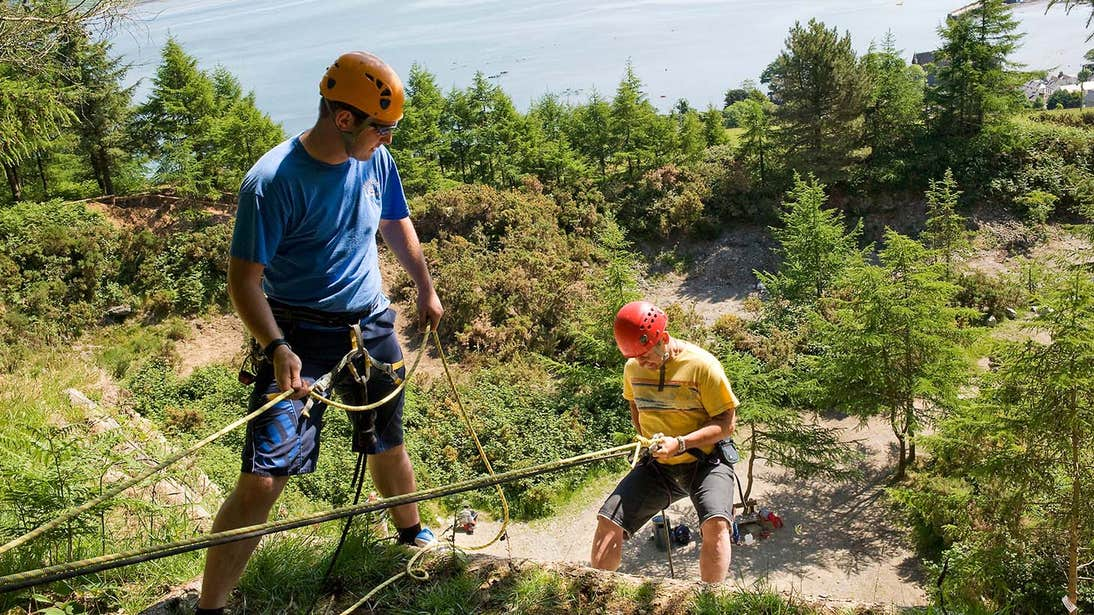 Man in blue using a rope to get down a slope with a person in a yellow tshirt