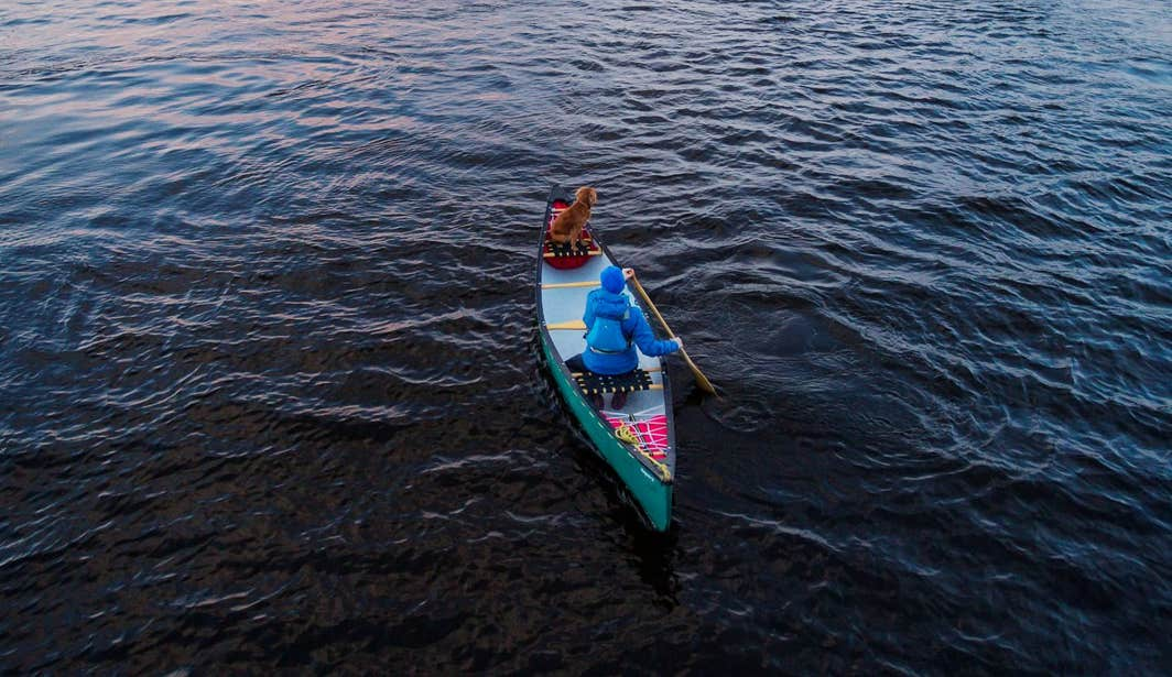 A woman paddling with a dog on Lough Derg.