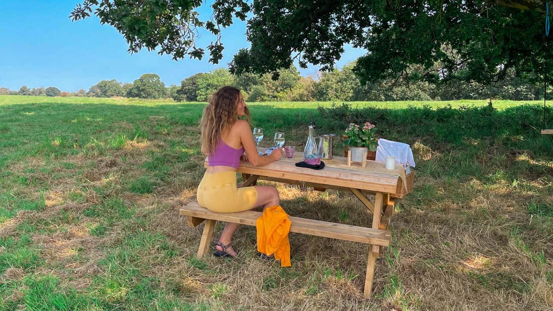 Roz Purcell sitting at a picnic table under a tree at Yew Point, Westmeath