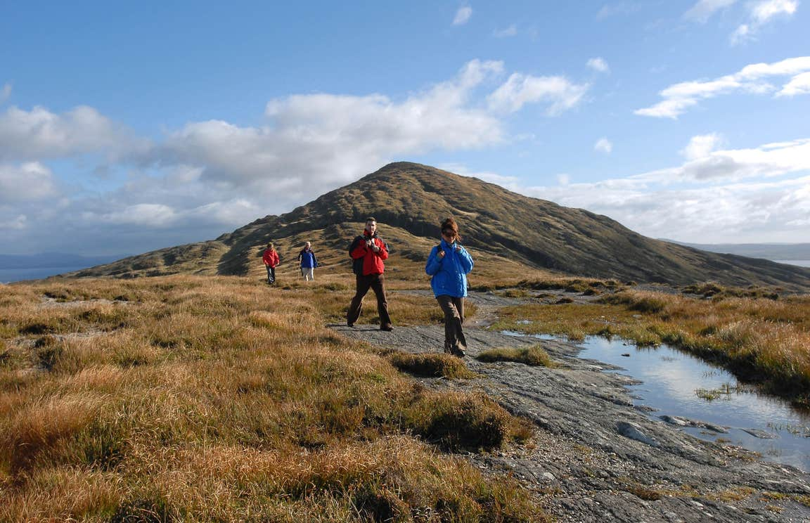 People walking at the base of a mountain on Sheep's Head, Cork