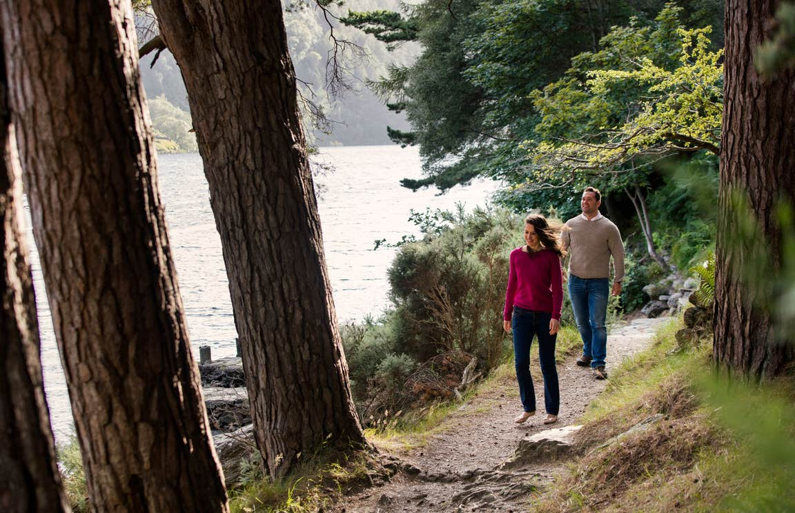 Couple walking on a trail beside a lake in Glendalough, Wicklow
