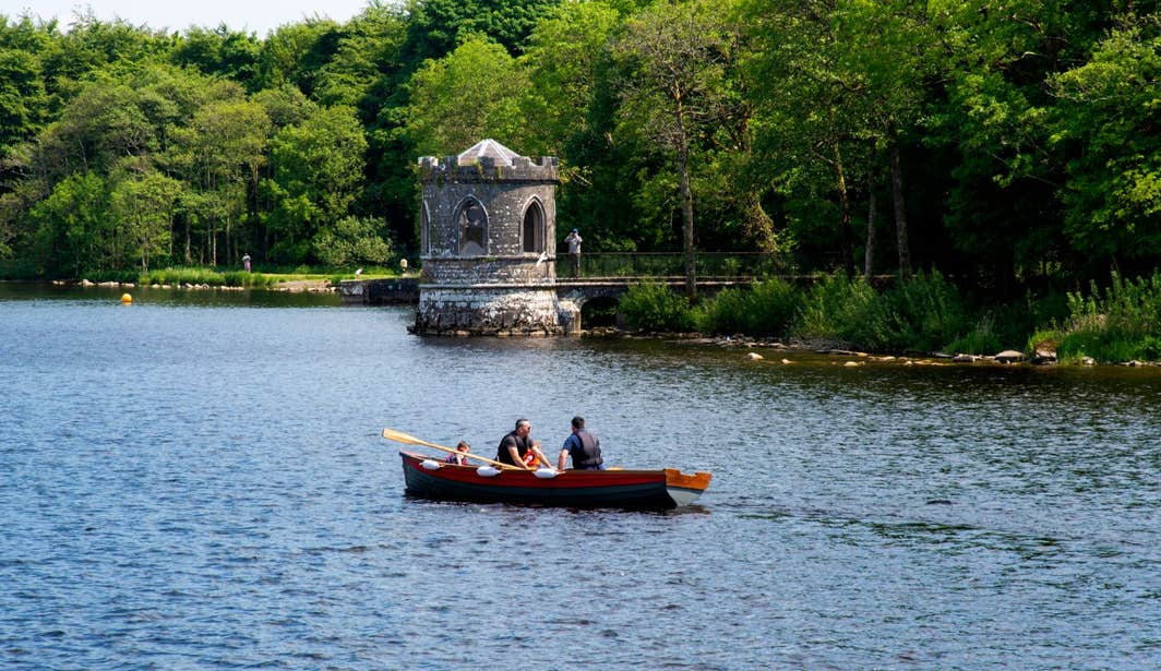 A small wooden row boat passing a castle on Lough Key.
