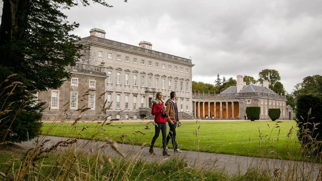 Two people walking on the grounds of Castletown House