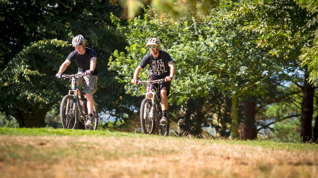 Two men biking uphill through thick trees