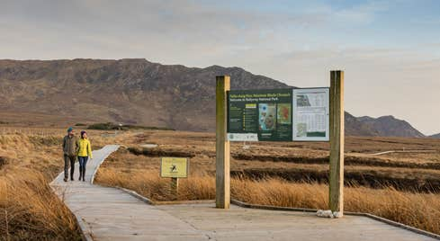 Two people strolling along the boardwalk at Wild Nephin Ballycroy National Park, Co. Mayo