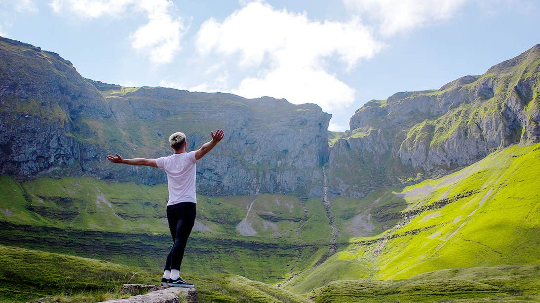 A person spreading their arms for a photo standing in the unique landscape of the Gleniff Horseshoe Drive, Sligo