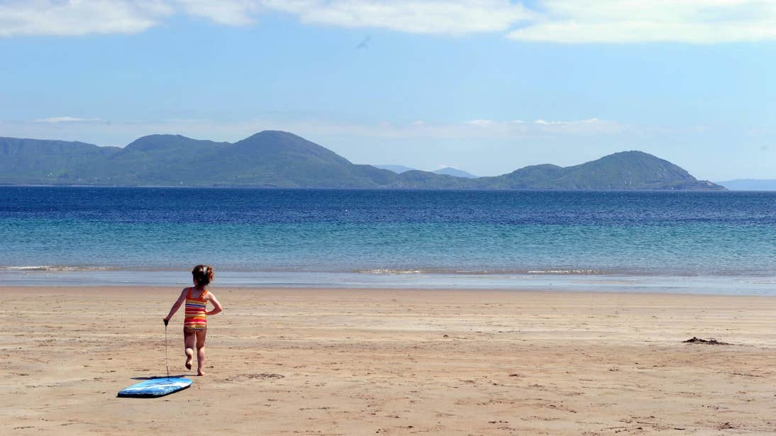 Little girl running on the sand towards the water at Ballinskelligs Beach in Kerry