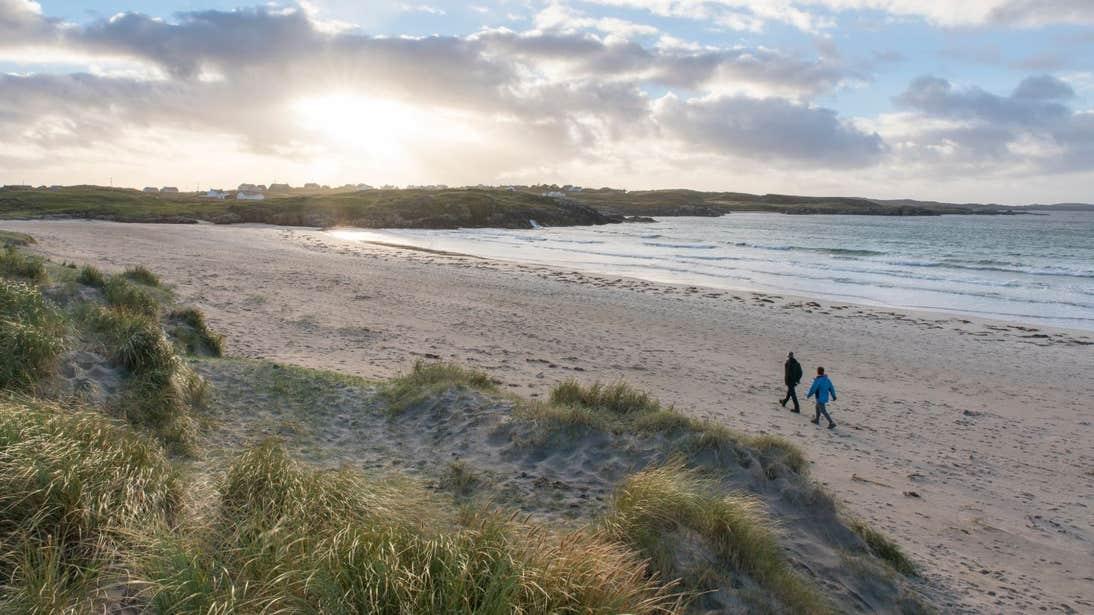 Two people walking down Carrickfinn Beach, Co. Donegal