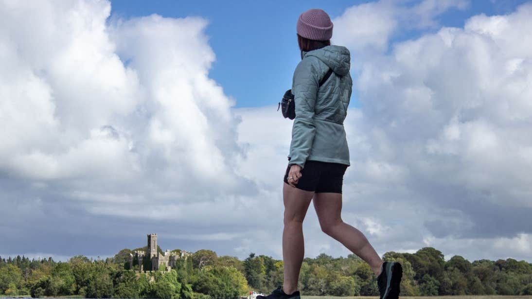 A girl walking with a view of a castle in the background at Lough Key, Roscommon