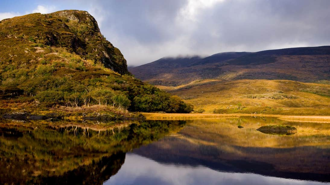 Rolling mountains beside lakes at Killarney National Park, Ring of Kerry, County Kerry on a cloudy day.