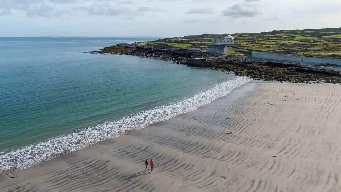 Two people walking own an empty Kilmurvey Beach Aran Islands, Galway