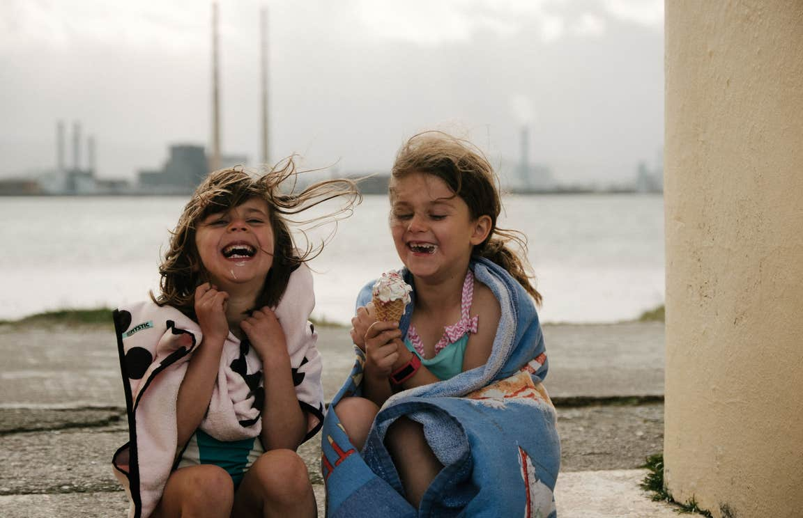 Two girls laughing and eating ice cream cones