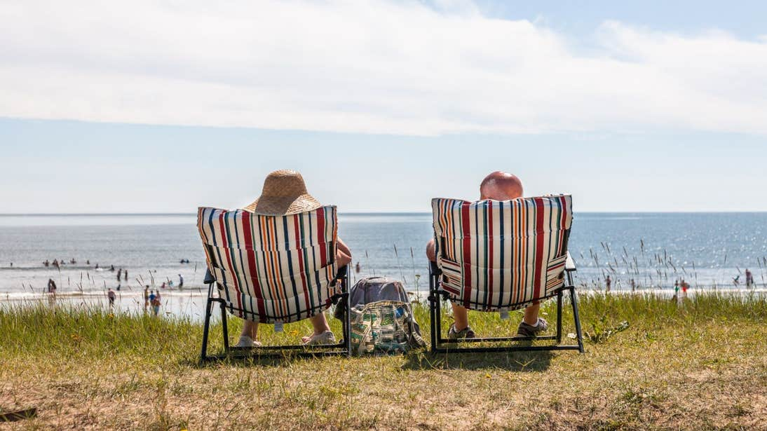 Two people relaxing on sunloungers at the beach