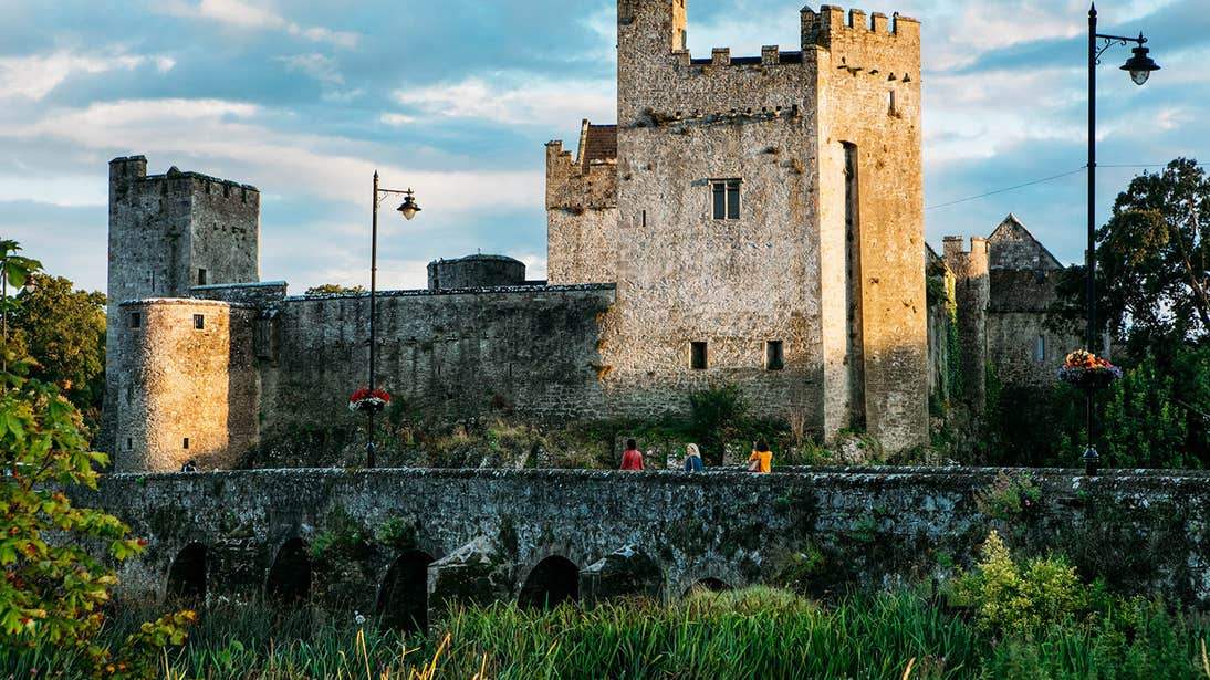 A group of people walking over a bridge to Cahir Castle, Tipperary