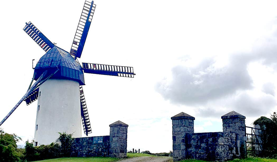Blue windmill behind a stone wall at Skerries Mills in Dublin.