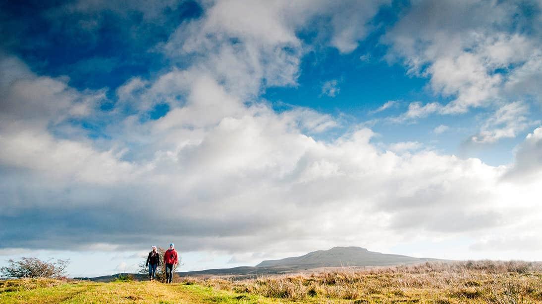 Blue skies at Cavan Burren Park as two people walk along one of the trails
