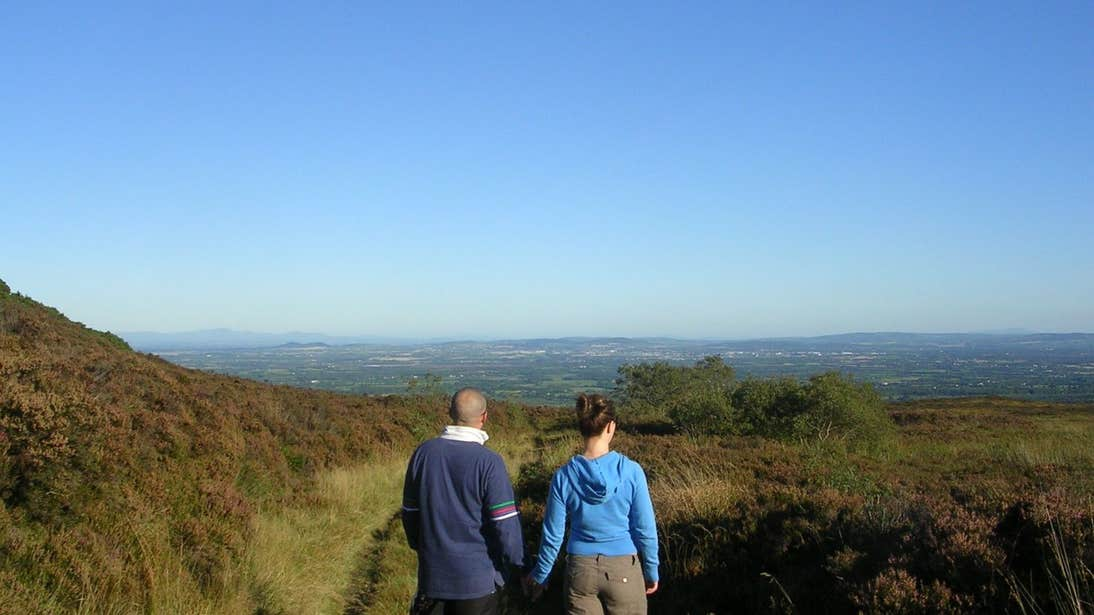 A man and woman holding hands looking out at blue skies and mountain views