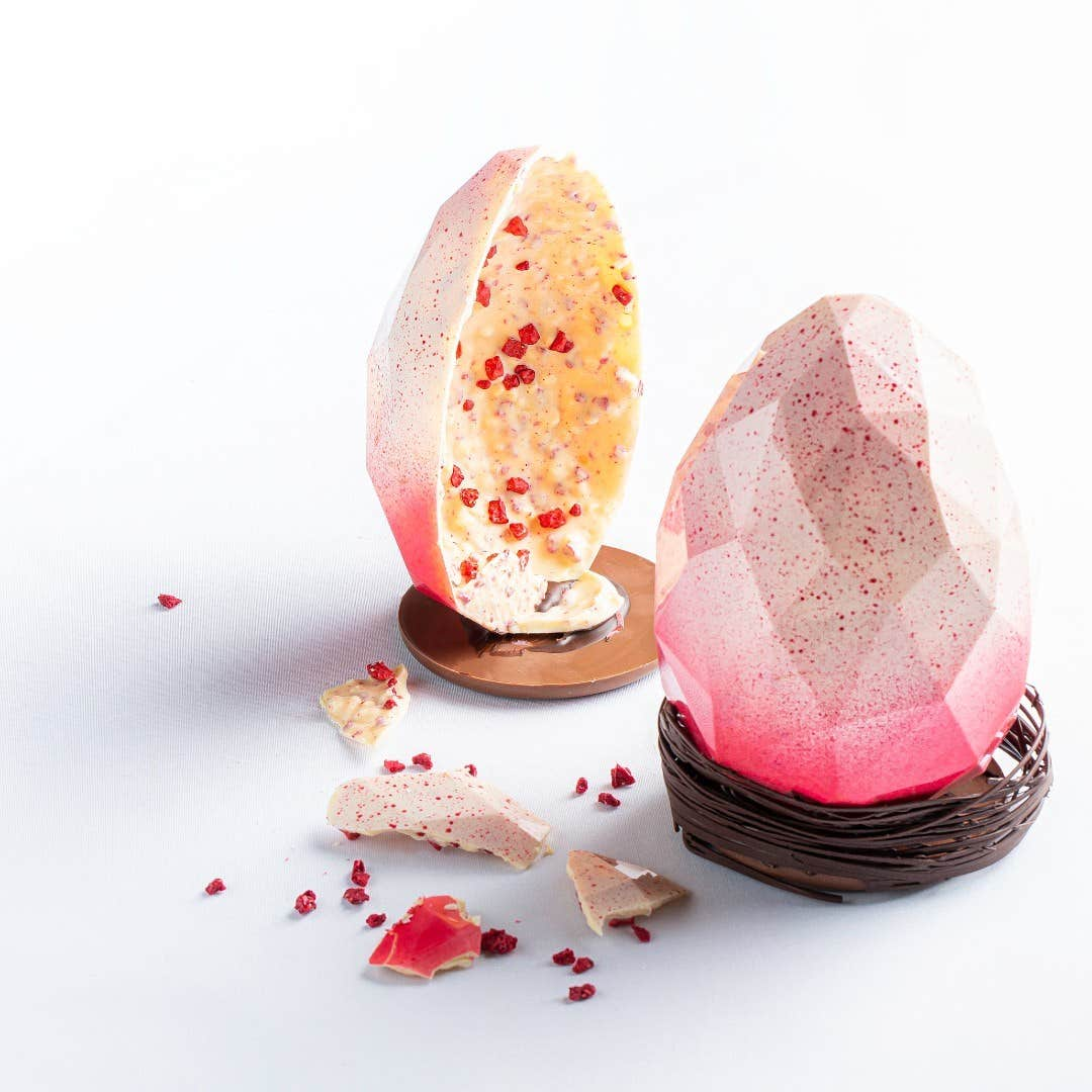 A pink and white chocolate Easter egg split in two made by Arcane Chocolate