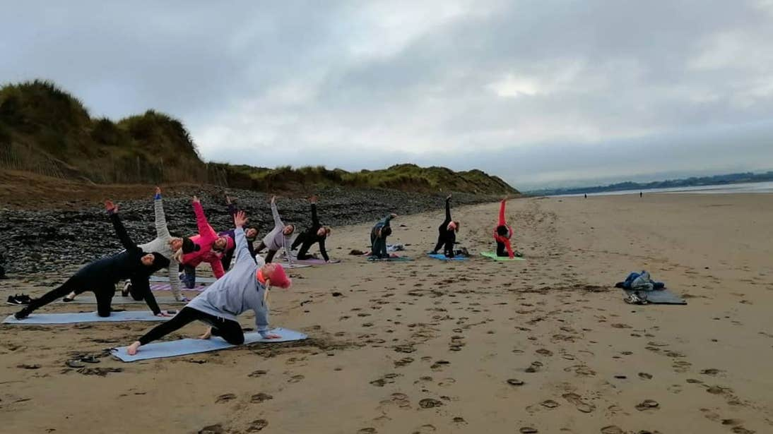 A group of people enjoying a yoga session on the beach in Strandhill, Sligo.