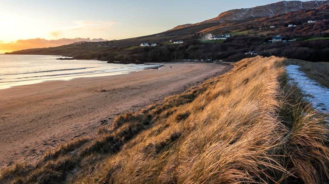 Sand dunes and a backdrop of mountains dotted with houses at Fintra Beach, Donegal