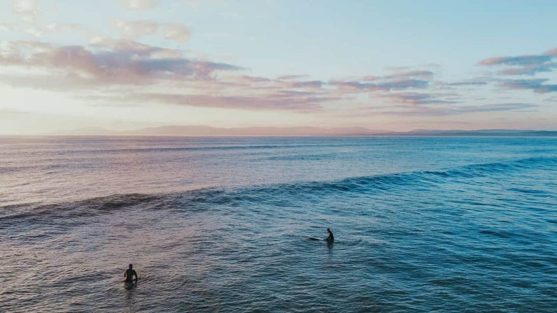 Two people surfing under pastel pink skies at Rossnowlagh Beach, Donegal