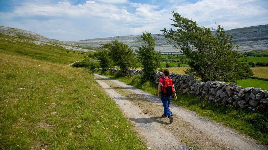 A person dressed in walking gear walking down a road near The Burren